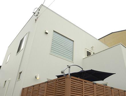 開放的なウッドデッキとルーフバルコニーのあるキューブ型住宅